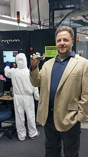 Eric MacDonald, Ph.D., associate director of the W.M. Keck Center for 3-D Innovation, displays a sample of what can be created with a metals printer using the lab's electron beam melting system.