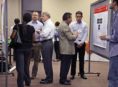 Researchers explain their posters at the 2014 UTEP IDR Symposium in April.