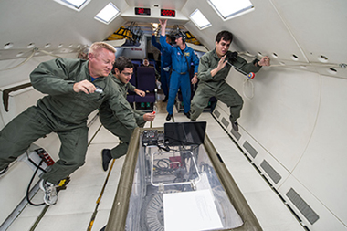 UTEP students Edgardo Flores, middle, and Sergio Cordova, right, float alongside NASA mentor Timothy Pelischek, left, on board a reduced gravity aircraft flight on July 10 in Ellington Field at NASA's Johnson Space Center.
